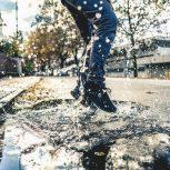Person splashing in rain puddle; rainwater; rain harvesting; rainfall